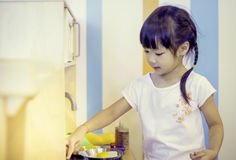 Asian girl playing toy kitchen Stock Images