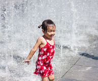 A asian girl playing by water fountain Royalty Free Stock Image