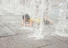 A asian girl playing by water fountain Stock Photo