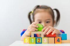 Asian girl playing wooden building blocks. stock photos