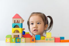 Asian girl playing wooden building blocks. stock images