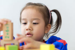 Asian girl playing wooden building blocks. royalty free stock images