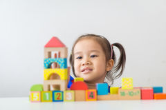 Asian girl playing wooden building blocks. royalty free stock photo