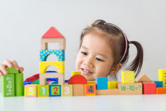 Asian girl playing wooden building blocks. stock image