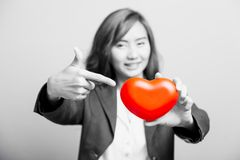Asian girl point to a red heart  focus at the heart Stock Photo