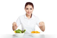 Asian girl point to salad and crisps bowls Royalty Free Stock Photo