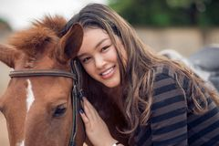 Asian girl and pony. Close-up portrait of Asian girl hugging her bay pony Stock Images