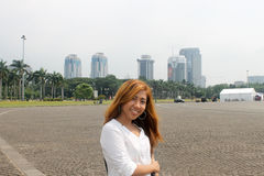 Asian girl posing in Monas, Jakarta with view of skyscrapers.  stock images