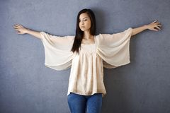 Asian girl posing by wall Royalty Free Stock Images