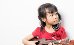 Asian girl is practicing guitar and wearing headphone Stock Photography