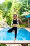 Asian Girl practicing yoga. Beautiful Asian Girl practicing Vriksasana Standing asana yoga pose by the pool Stock Image