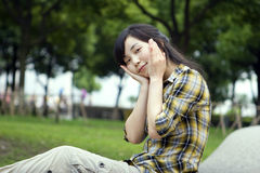 Asian girl in a prak. Asian girl poses a smile with fingers close to her face in a park with green trees and grassland Stock Image