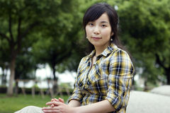 Asian girl in a prak. Asian girl sits in  a park with green trees and grassland Royalty Free Stock Photography
