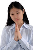 Asian Girl Praying. Young Asian woman bows her head in prayer stock photo
