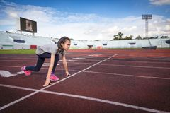 Asian girl prepare to run in the starting point at the racetrack, running and exercise for health royalty free stock images
