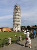 Asian girl pushing over the tower of Pisa Royalty Free Stock Photos