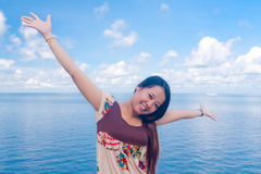 Asian girl raise arms at sea Royalty Free Stock Photos