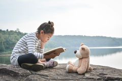 Asian Girl Reading A Book With Teddy Bear On Nature,alone Girl , Stock Image