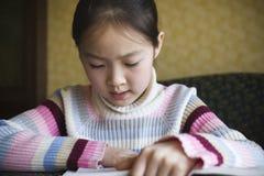 Asian girl reading a book. 9-year old asian girl reading a book Royalty Free Stock Photos