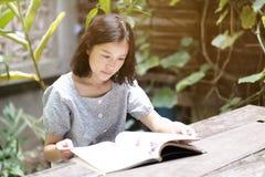 Asian girl reading a book in the backyard garden
