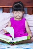 Asian girl reading a book. Education concept. A little cute asian girl in a purple dress reading a book sitting on bed in bedroom. Preschoolers learn and study Stock Image