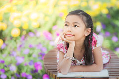 Asian Girl reading a book. In the flower park in relax action Royalty Free Stock Photos