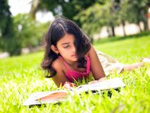 Asian girl reading a book in the park Stock Photos