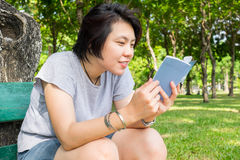 Asian girl reading book in the park Stock Images