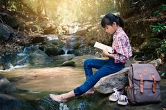 Asian girl reading a book sitting on the rock near waterfall in forest background Royalty Free Stock Images