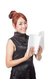 Asian girl reading a book and smile look at the camera Stock Photography