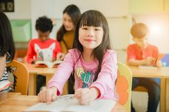 Asian girl reading a book smiling at the camera. Row of multiethnic elementary students reading book in classroom at school.