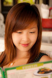 Asian girl reading memu in restaurant Royalty Free Stock Image