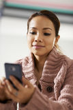 Asian girl reading sms on smarthphone Royalty Free Stock Images