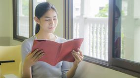 The asian girl reads a red book Stock Photos