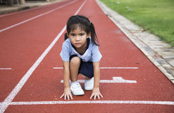 Asian girl runng outdoor game. Asian girl ready to start running game on the line of outdoor arena Stock Photography