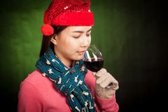 Asian girl with red christmas hat drink red wine Royalty Free Stock Photo