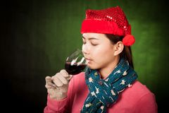Asian girl with red christmas hat drink red wine Stock Image