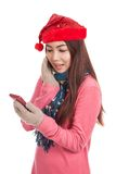 Asian girl with red christmas hat excited with mobile phone Royalty Free Stock Photos