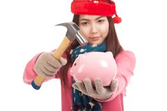 Asian girl with red christmas hat ,hammer and piggy bank Royalty Free Stock Photos