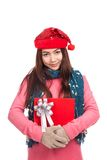 Asian girl with red christmas hat hugs a gift box Royalty Free Stock Photos