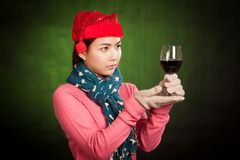Asian girl with red christmas hat look at glass of wine Royalty Free Stock Photography