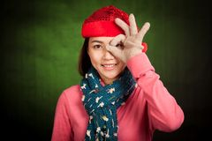 Asian girl with red christmas hat with OK hand over eye Royalty Free Stock Images