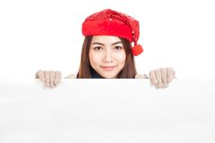 Asian girl with red christmas hat peeking from behind blank bann Royalty Free Stock Images