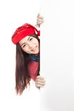 Asian girl with red christmas hat peeking from behind blank bann Stock Photo