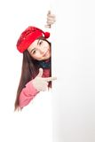 Asian girl with red christmas hat peeking from behind blank bann Stock Photography