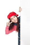 Asian girl with red christmas hat peeking from behind blank bann Royalty Free Stock Photo