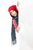 Asian girl with red christmas hat peeking from behind blank boar Royalty Free Stock Photography