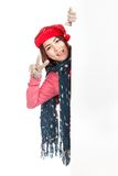 Asian girl with red christmas hat peeking from behind blank boar Royalty Free Stock Photo