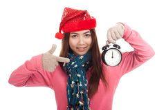 Asian girl with red christmas hat point to alarm clock Stock Photos