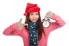 Asian girl with red christmas hat point to alarm clock Royalty Free Stock Images